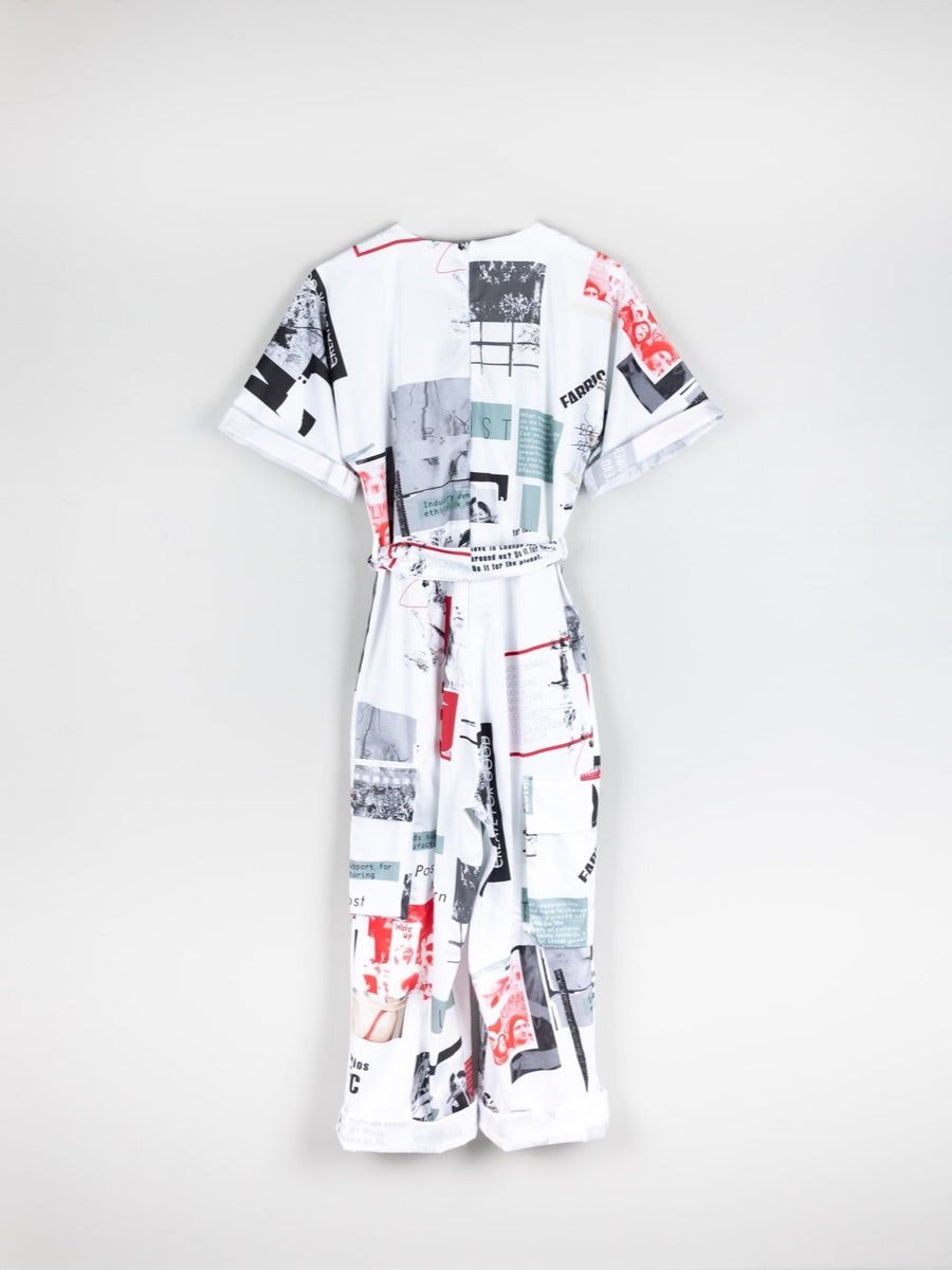 White based red & black printed jumpsuit, short sleeved with a belt. This printed white jumpsuit has sustainability activist messaging and is made by ethical clothing brand Fanfare Label