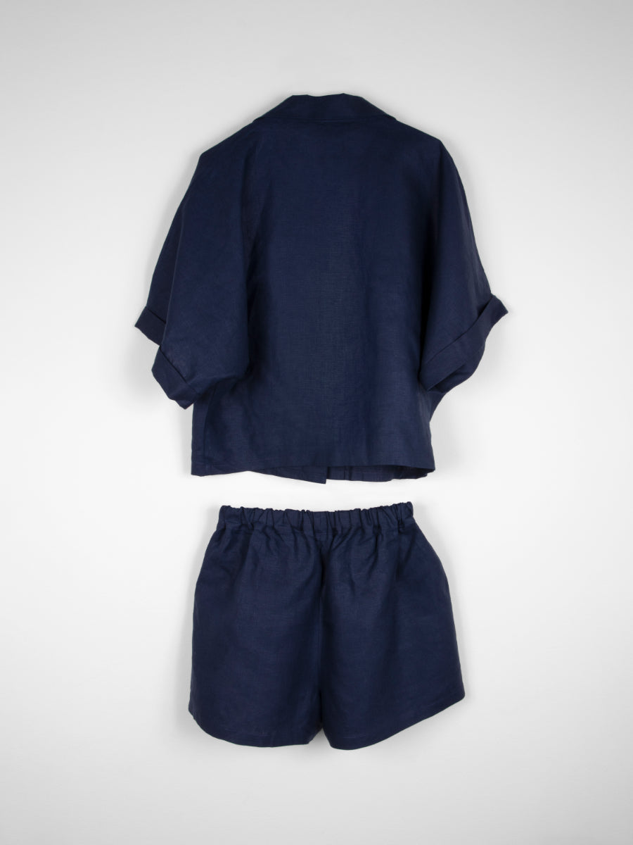 Our Navy Linen Summer Co-ord Set is an essential summer set comprised of a low cut v-neck button-down shirt and shorts, perfect for the summer. Fanfare Label