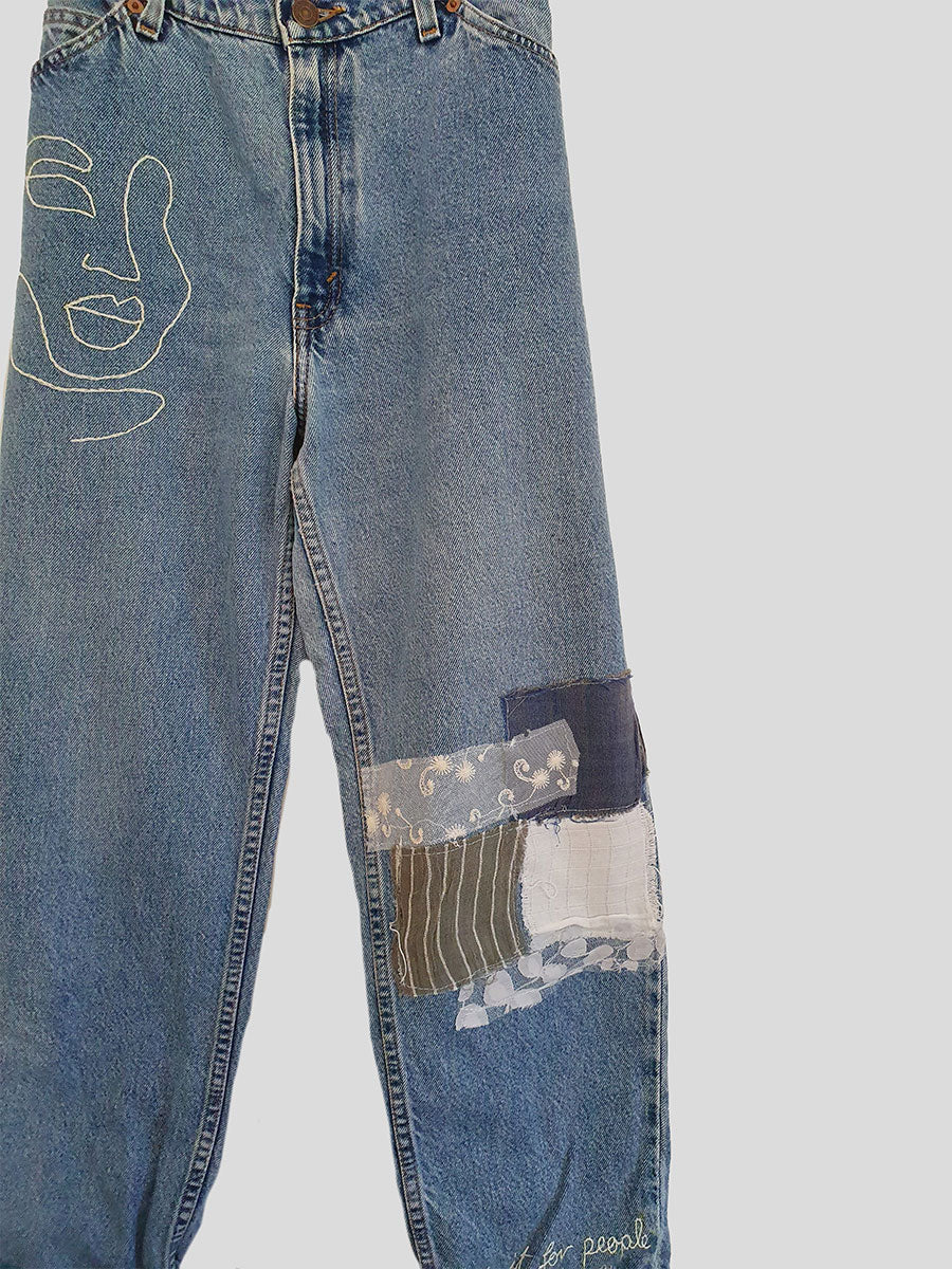 These high waisted jeans have been embroidered with an abstract face below the right pocket and patched with upcycled offcuts below the left knee. A one-of-a-kind designer piece, these jeans are hand-embroidered in Fanfare's sustainable factories based here in the UK.