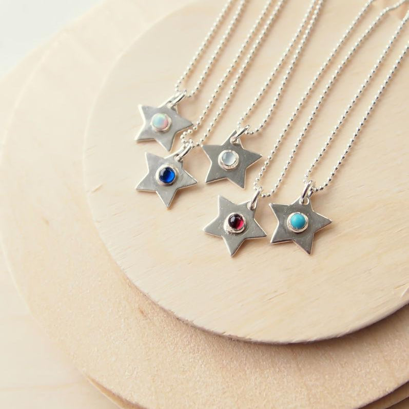 Silver star pendants with different coloured gemstones