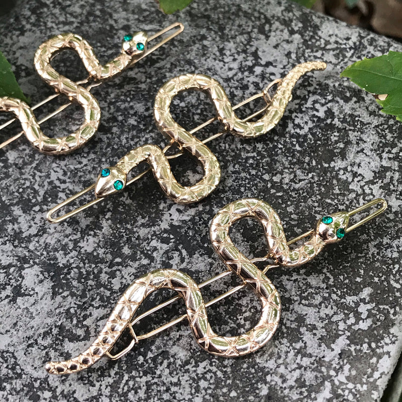 Gold tone snake barrettes with green rhinestone eyes