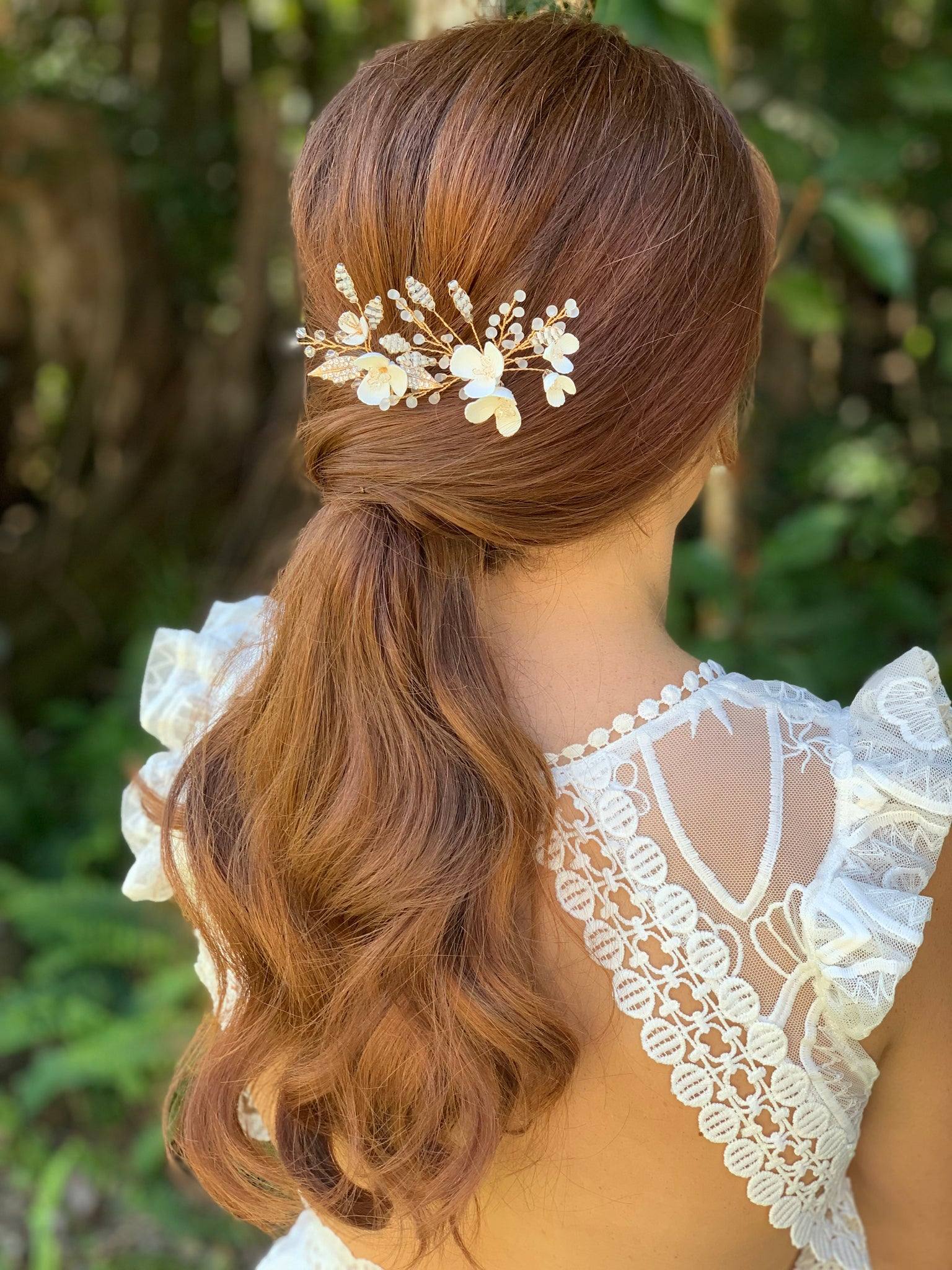 Low volume ponytail with two gold bridal hair pins with white flowers