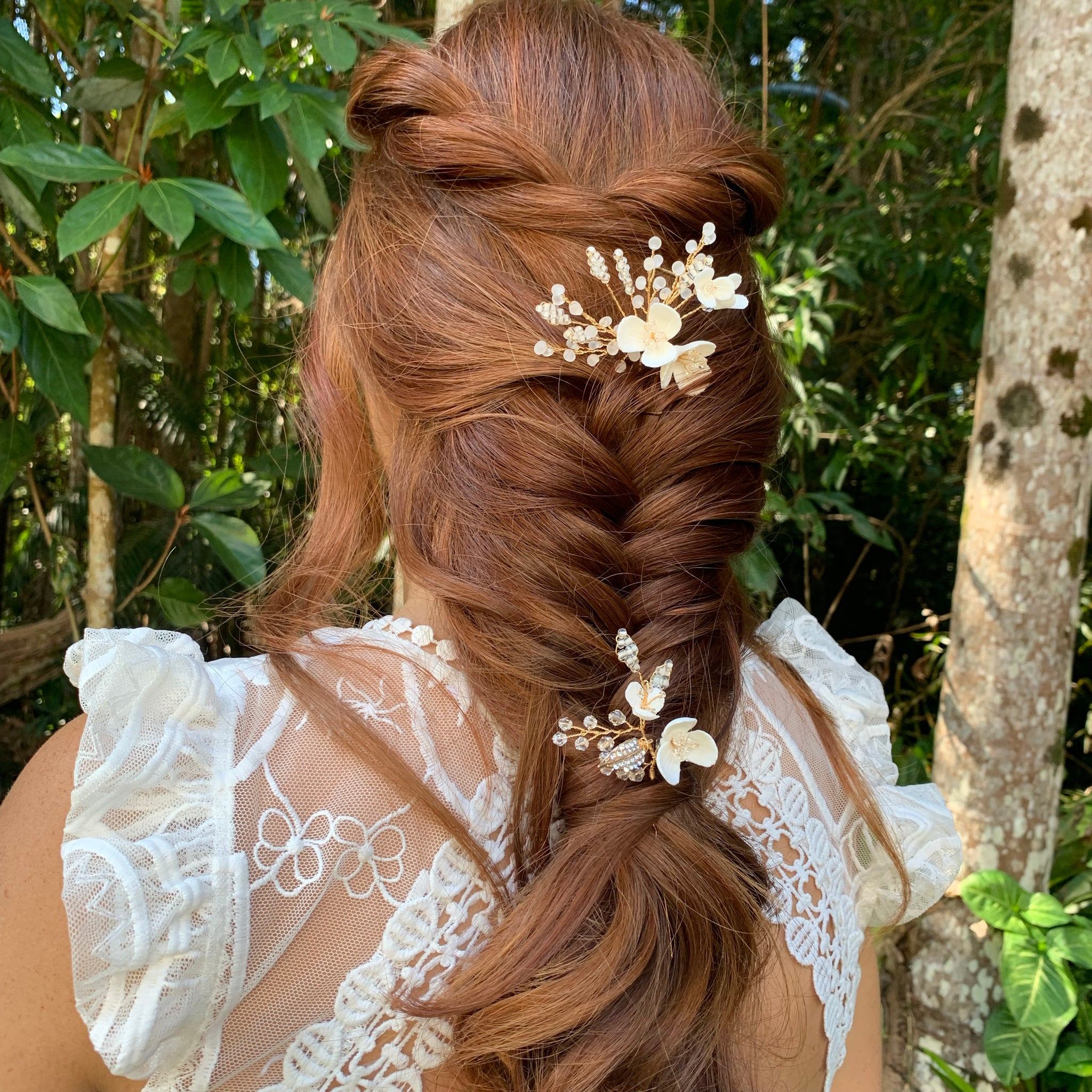 fishtail braid bridal hairstyle with gold hair accessoires with white flowers