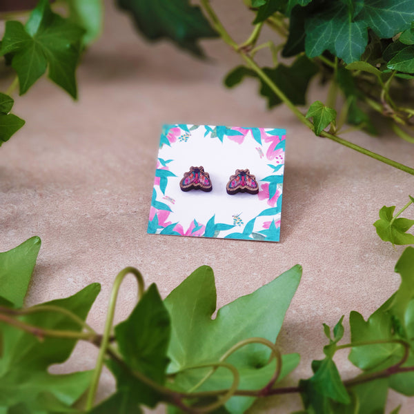 A pair of moth stud earrings illustrated by Ilana Ewing in shades of pink, orange and green.