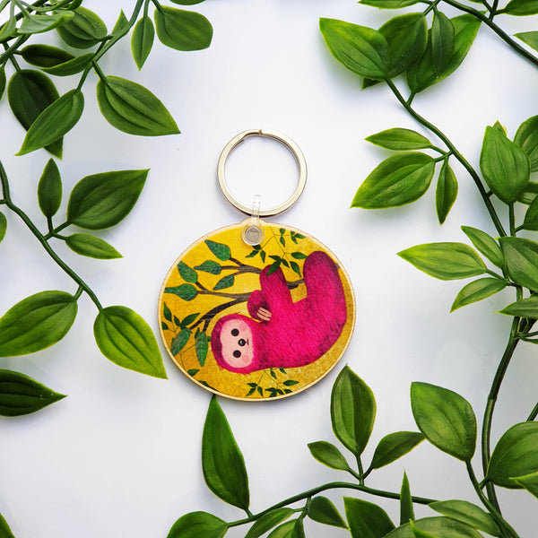 Wooden Pink Sloth keychain on a yellow background with leaves