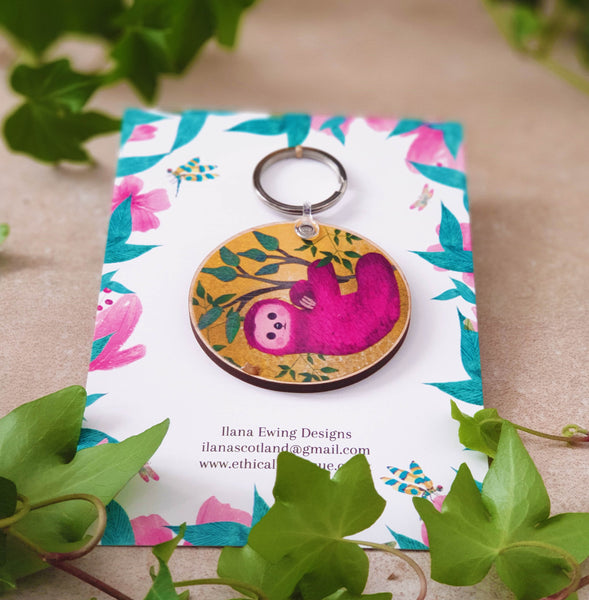 Pink Sloth keychain on a yellow background with leaves packaged in a illustrated card