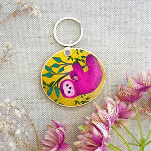 Pink Sloth keychain on a yellow background with leaves