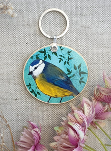 Blue round wooden keychain with a blue tit design