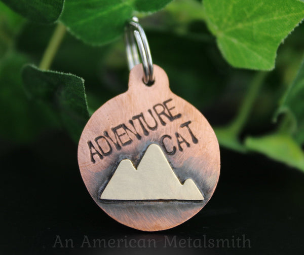 Copper pet tag with Adventure Cat stamp and mountain range brass addition made by An American Metalsmith