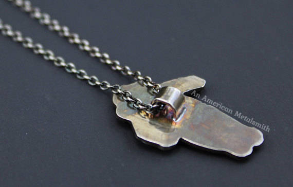 Rear side of a sterling silver astronaut necklace made by An American Metalsmith