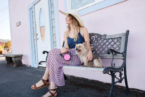 Woman sitting with small dog using Wigzi Retractable Dog Leash with Gel Handle in Pink