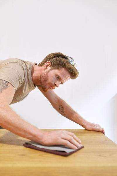 a man standing on top of a wooden table