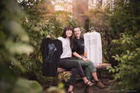 Janie Boivin, left, and Lara Kelly, right, sit amongst greenery and nature holding up their products.