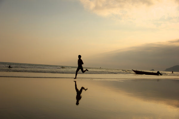 silhouetted runner on a beach at sunset