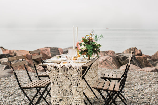 lovely table set for a dinner date on a rocky shore