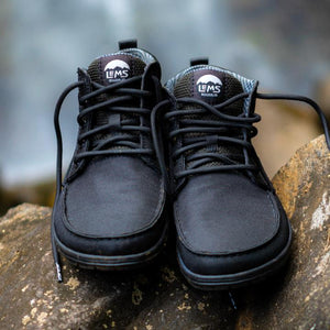 Pair of Lems Boulder Boot Mid on rocks