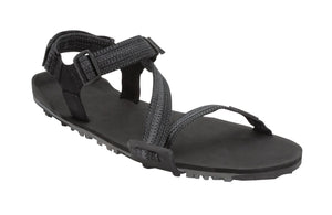 Z-Trail in black - flat black sport sandal with z-shaped strapping at the front and an adjustable ankle strap at the back. Two black slide buckles are shown at the side of the sandal
