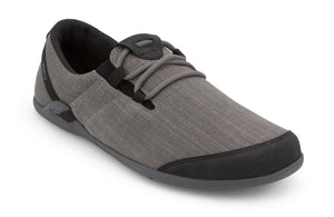 Image of a gray hemp slip-on shoe from an angle that shows the front and side of the shoe. Minimal gray laces criss-cross through black loops and the toe box is capped in dark gray. The soft black inner lining can be seen in the image. White background.