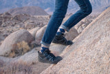 In a Rocky area, a pair of legs climbs uphill wearing DayLite Hiker Fusion Hikers