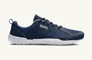 Image of a minimal running shoe from a side view. The upper part of the shoe is made of dark blue microfibre with slightly lighter blue diamond-pattern mesh details. Back loop and laces are dark blue, with white stitching and white soles. White background.