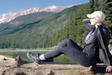 Woman resting on log near mountain lake wearing Xcursion Fusion Spruce style