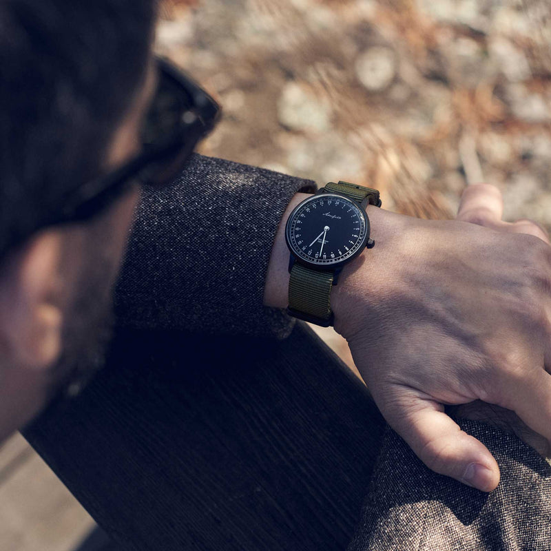 24-hour watch with matte black case and green NATO strap