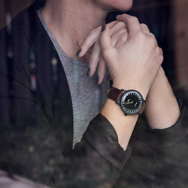 24-hour watch with matte black case and brown leather strap