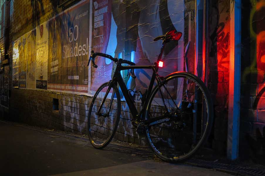 Bicycle in dark laneway outside a train station