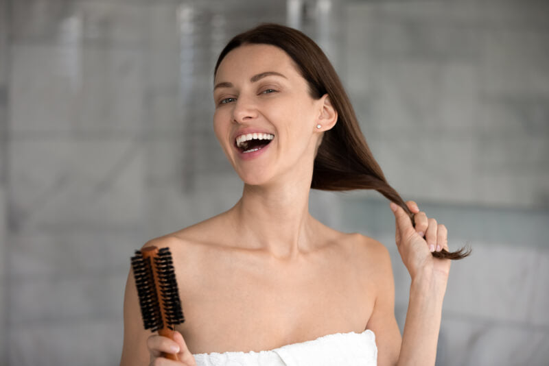 happy young woman holding her long dark hair