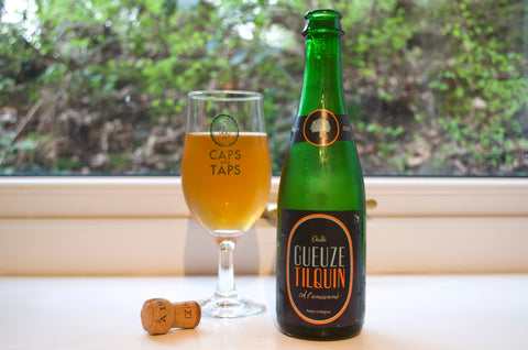 Tilquin Gueuze a l'Ancienne in a Caps and Taps glass with the cork in front. The beer is a slightly hazy dark amber colour.