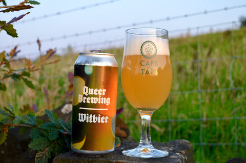 Queer Brewing Flowers Witbier in a Caps and Taps glass on a stone wall in a field. The beer is a hazy amber colour with a fluffy white head