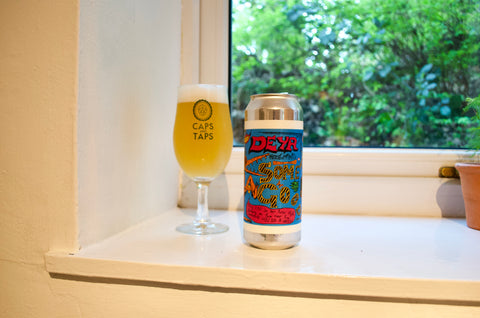 DEYA Something Good 13 IPA can on a shelf poured out in a Caps and Taps glass. The beer is a hazy gold colour.