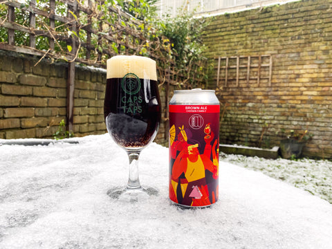 A glass of Chosen Family American brown ale by Mondo and Queer Brewing. The beer is a dark brown, almost black, with light brown head. The glass and can are on a snowy table in a garden