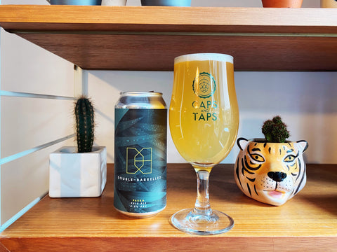 Double-Barrelled Parka Pale Ale poured in a Caps and Taps glass on a shelf surrounded by plants