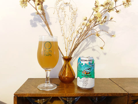 Lervig No Worries alcohol-free pale ale poured into a Caps and Taps glass with a vase of dried flowers behind. The beer is a hazy yellow-orange colour.
