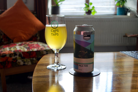 Pressure Drop Pale Fire American pale ale poured in a Caps and Taps glass on a coffee table. The beer is a clear, pale golden yellow