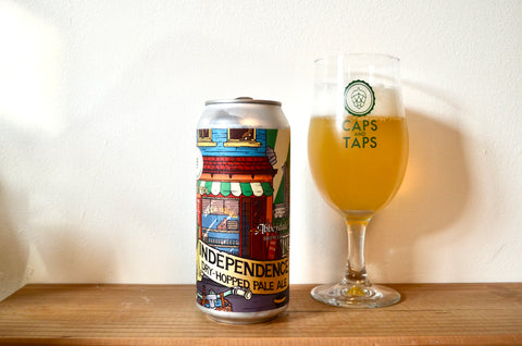 Abbeydale Independence pale ale poured into a Caps and Taps tulip glass. The beer is a hazy golden orange.