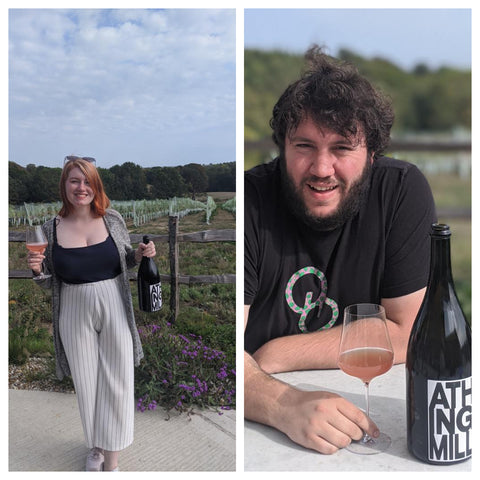 Steph standing up holding a bottle and glass of Athingmill Tillingham sparkling wine, and Phill sitting down with a bottle and glass.