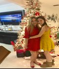 Photo of two women in front of a christmas tree