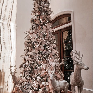 A pink and white Christmas Tree with silver reindeer made by interior designers