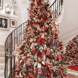 A red and white themed Christmas tree by a spiral staircase