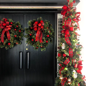 Front doors with Christmas wreaths with a thin Christmas tree nearby