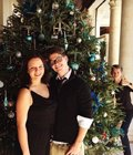 Two people standing in front of a christmas tree
