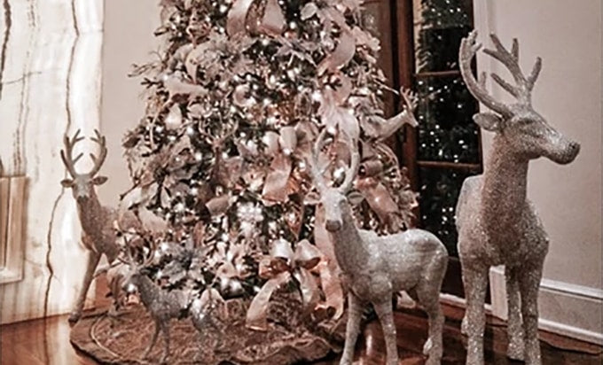 A pink and white themed Christmas tree with silver reindeer