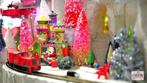Coca-Cola train moving through a Christmas village