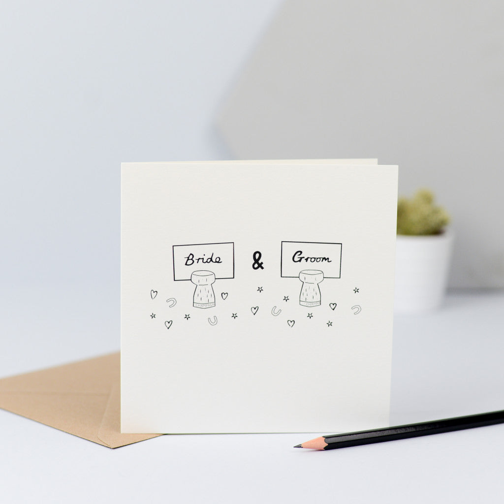 A sweet design with a hand drawn illustration of two champagne corks with the place names for the Bride and Groom stuck in them and surrounded by confetti.