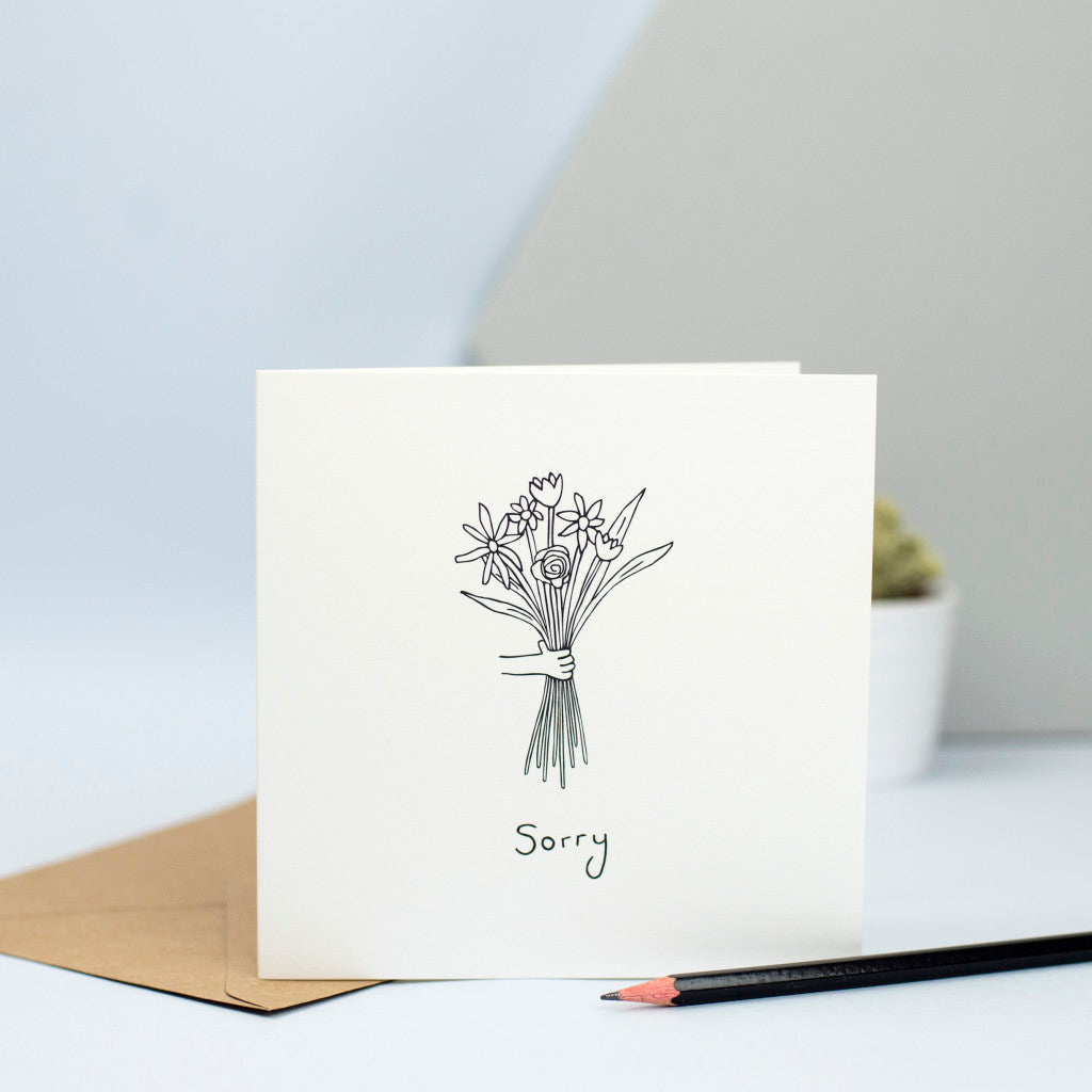 A sympathy card with a hand holding a bunch of flowers.