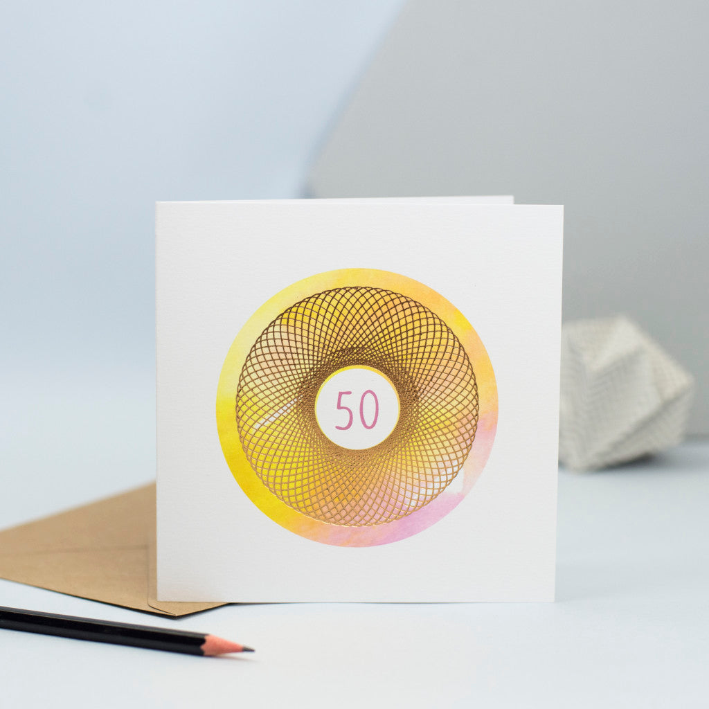 A 50th birthday card featuring a gorgeous pink and yellow watercolour background and a gold foiled spirograph on top with the number 50 in the centre in pink