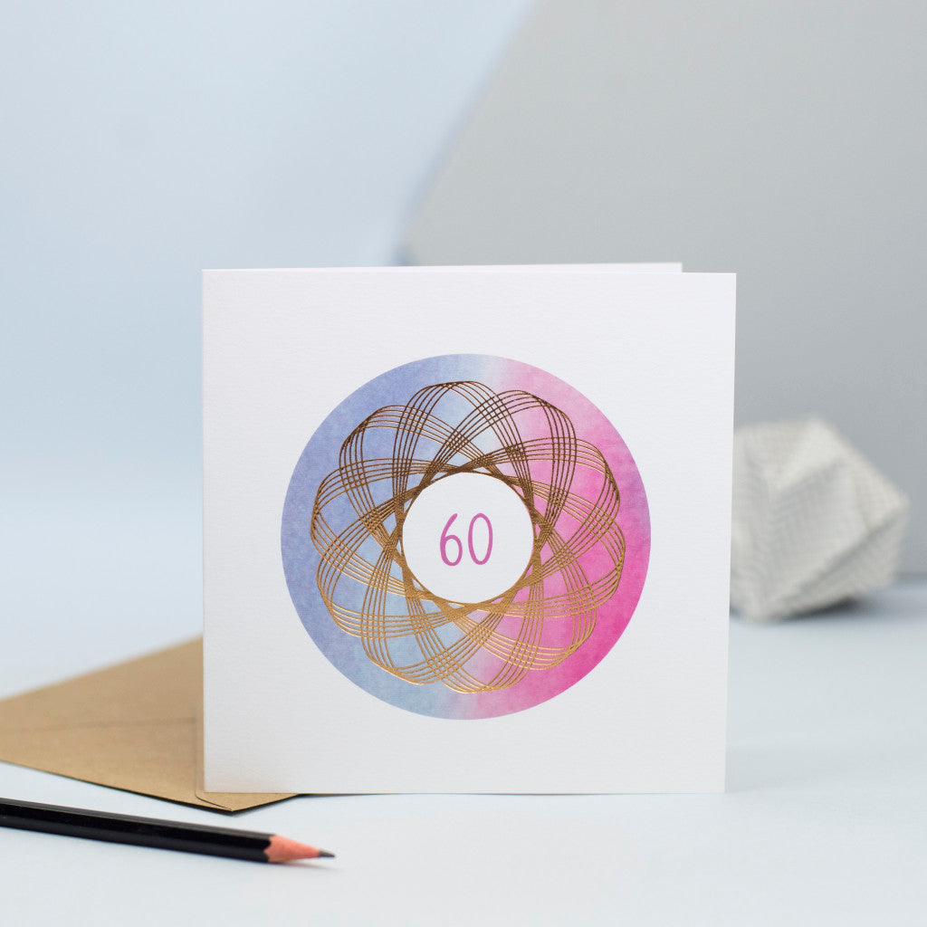 A luxury 60th birthday card with a gold foiled spirograph over a watercolour background.
