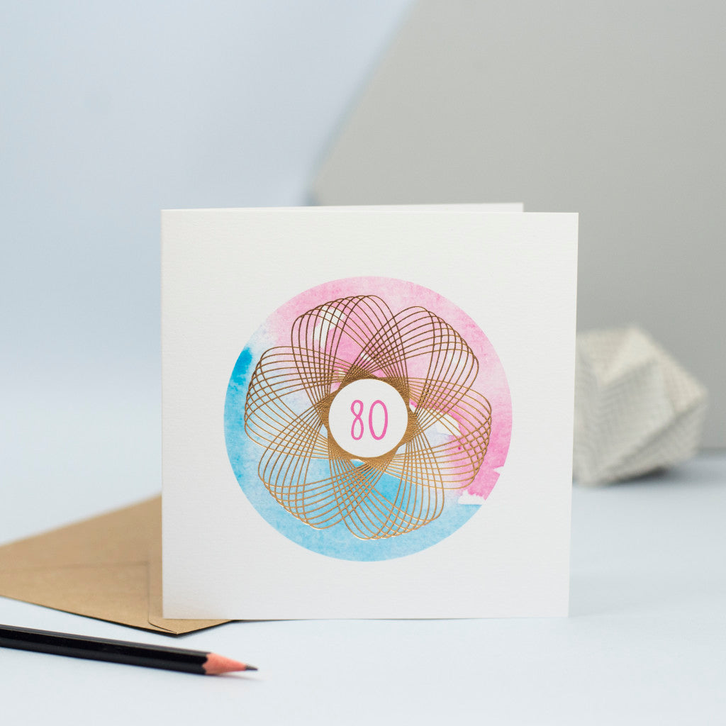 a pink and blue 80th birthday card with a gold foil spirograph